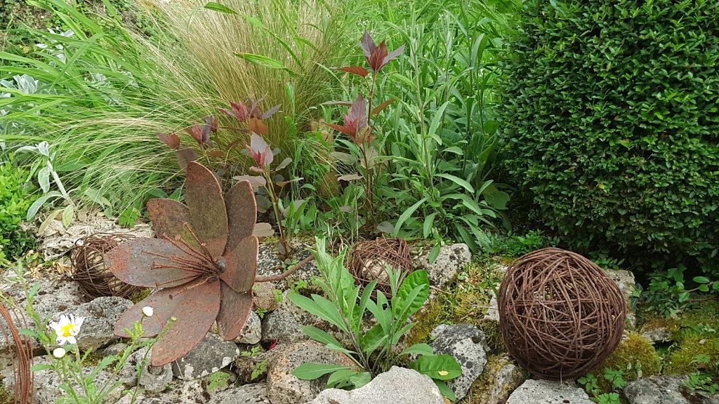 Au milieu des fleurs et pelotes de rouille, l'eupatoire rugeuse 'Chocolate'est quant à elle bien vivante...